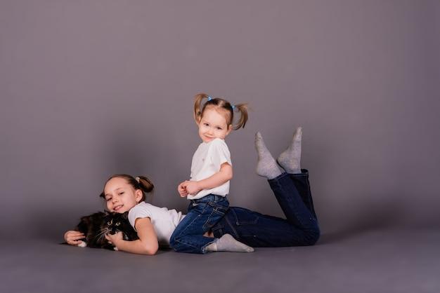 스튜디오에서 검은 고양이 포옹 두 여자 자매