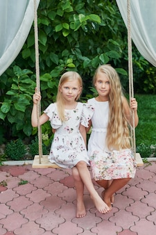 Two girls sisters ride on a swing in the summer in the garden