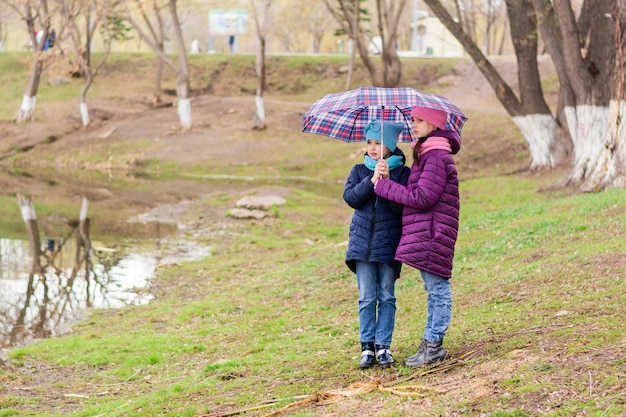 Two girls sisters stand under an umbrella on the shore of a lake in early spring. walk outdoors