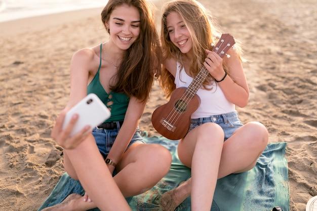 自画像を撮っているビーチに座っている2人の女