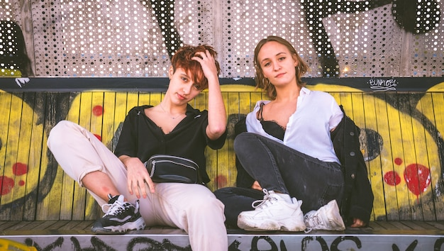 Two girls sitting on a bench against a wall full of graffiti on the street