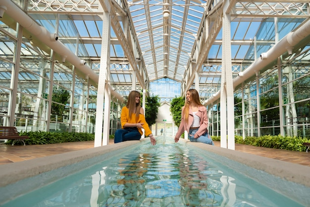 Two girls sitting on the edge of a fountain with water inside a bright greenhouse