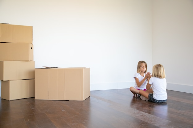 Two girls sitting on floor near heap of boxes in their new apartment and playing together