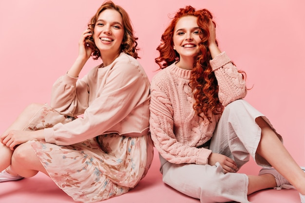Two girls sitting on floor with smile. studio shot of friends posing on pink background.