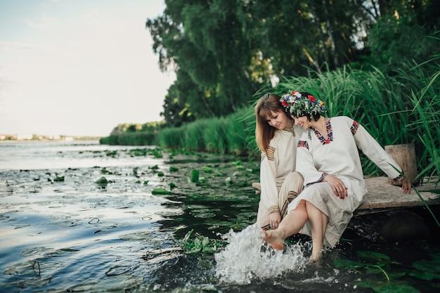 Две девушки сидят возле воды и играют