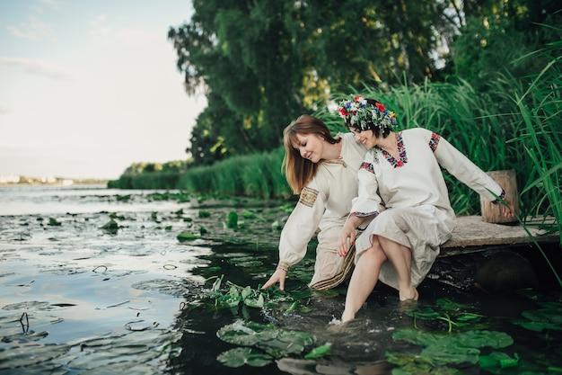Две девушки сидят возле воды
