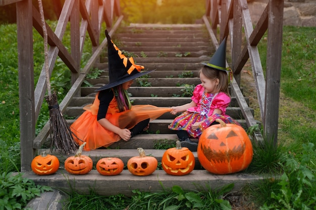 Two girls sitting on an old wooden staircase with carved pumpkins of halloween