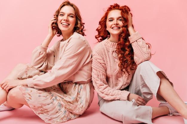 미소로 바닥에 앉아 두 여자입니다. 분홍색 배경에 포즈 친구의 스튜디오 샷입니다.