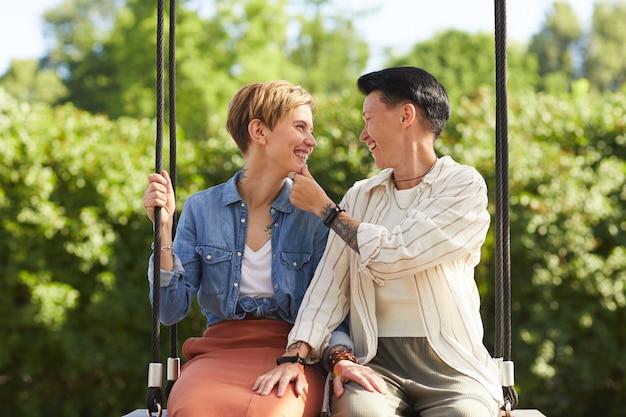 一緒にブランコに座ってお互いを見て笑っている2人の女の子
