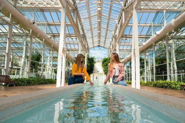 明るい温室の中の水で噴水の端に座っている2人の女の子
