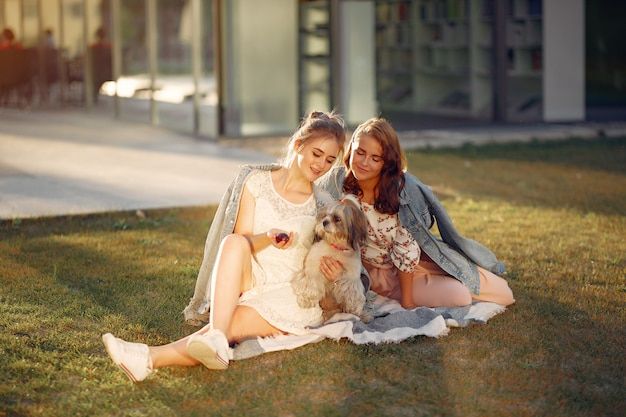 Two girls sitting in a park with a little dog