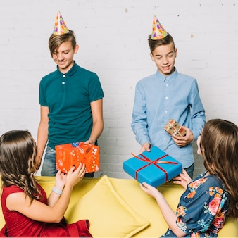 Two girls sitting on sofa giving presents to the smiling birthday boys