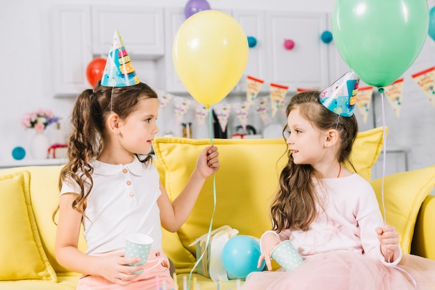 Two girls sitting on sofa holding balloon
