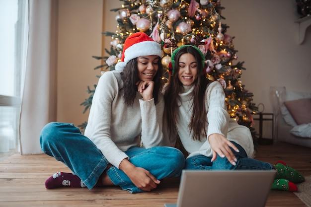 Due ragazze sorridenti mentre parlano con un amico in linea sul computer portatile durante la celebrazione del natale a casa