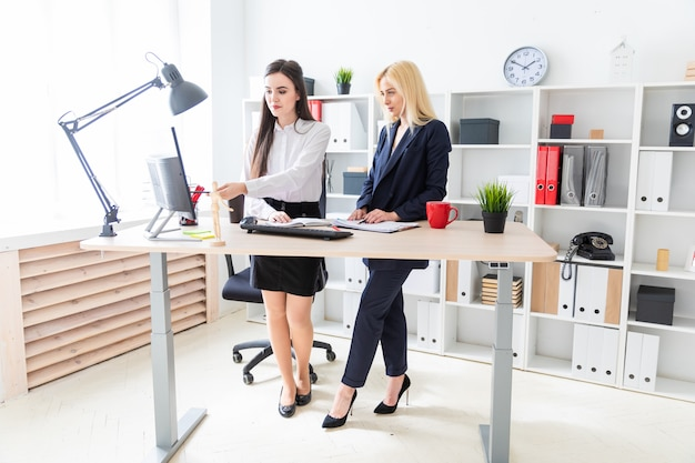 Two girls stand in the office near the table and look at the monitor.