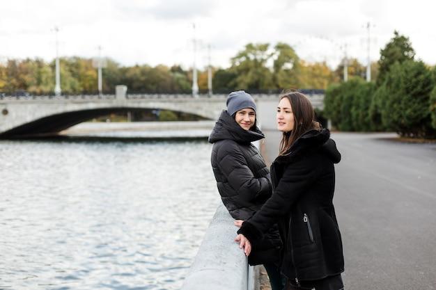 Две девушки стоят на набережной у воды, глядя в кадр. фото высокого качества