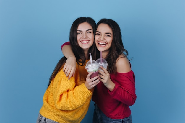 Two girls stand side by side and smile while they drink milkshake and a cocktail