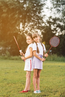 Two girls standing back to back holding badminton in the park