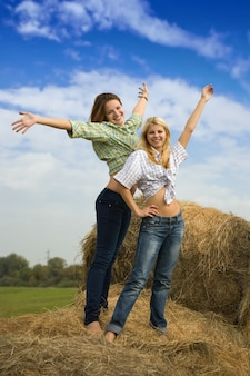 Two girls standing on hay