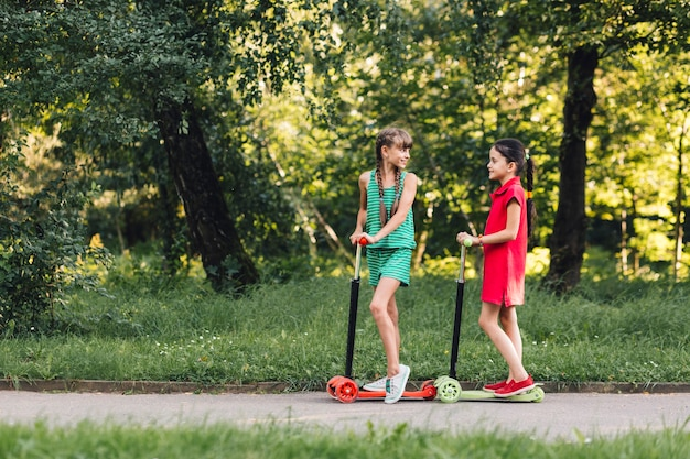 Two girls standing on kick scooter at countryside road