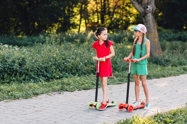 Two girls standing on push scooter looking at each other in the park