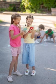 Две девочки стоят со смартфонами и рисуют на корточках мальчиков