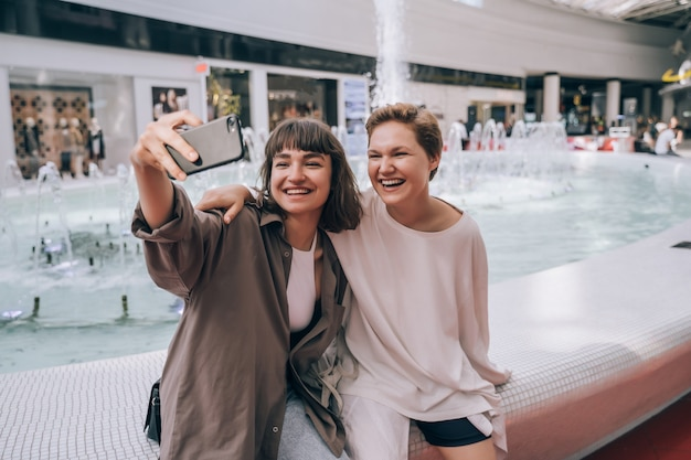 Две девушки делают селфи в торговом центре, у фонтана