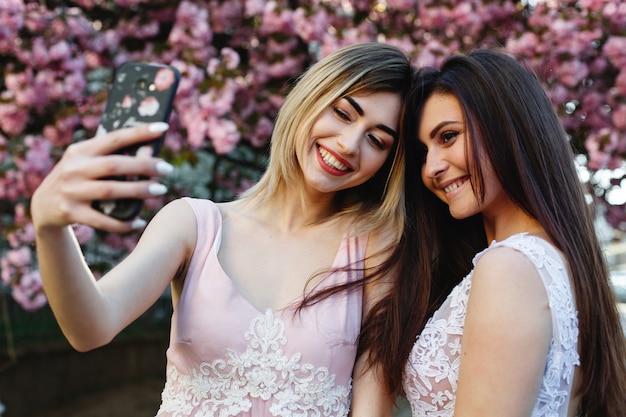 Two girls take selfie before a beautiful sakura tree in the park