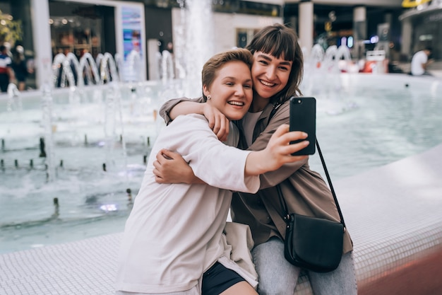 Two girls take a selfie in the mall, a fountain