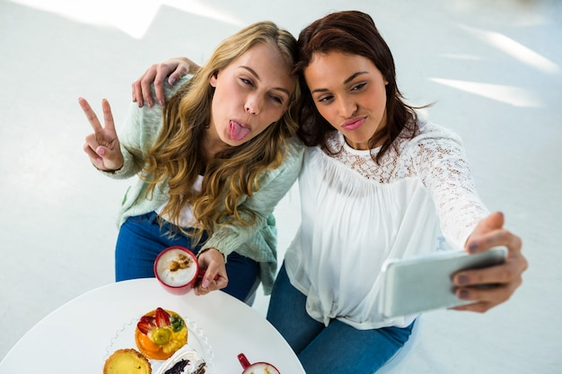 Two girls take a selfie while eating and drinking coffee