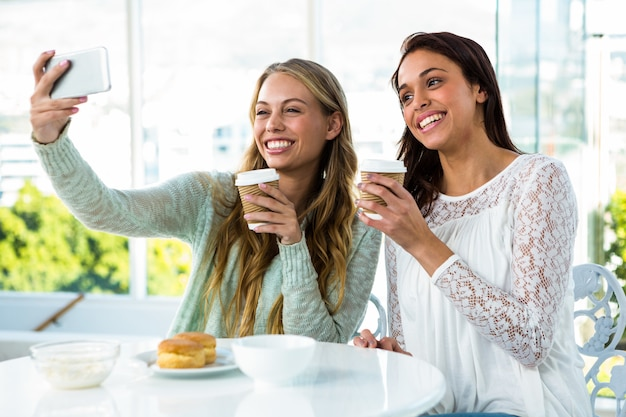 Two girls take a selfie while eating and drinking tea