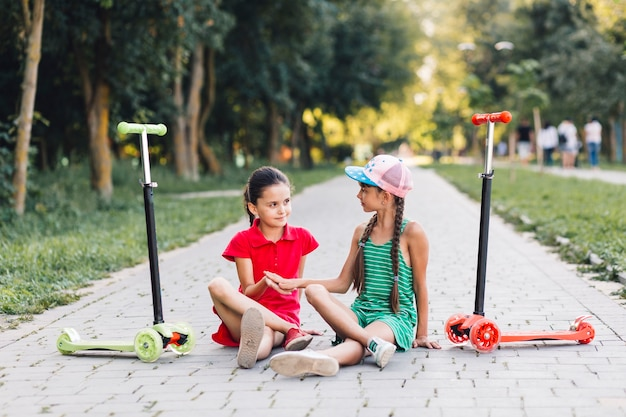Two girls touching each other's hand while sitting on walkway with their push scooters