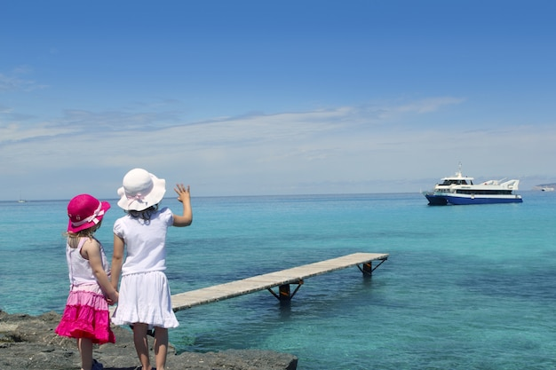 Two girls tourist turquoise sea goodbye hand gesture