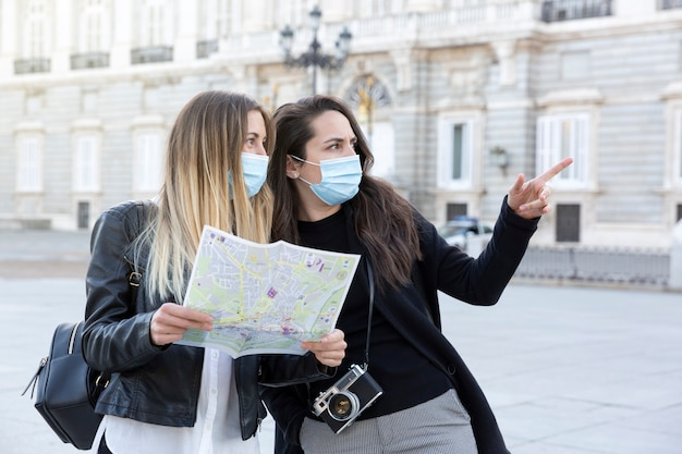 街を一緒に旅行する2人の女の子。彼らは観光地図を持っていて、医療用マスクを着用しています。旅行とニューノーマルのコンセプト。