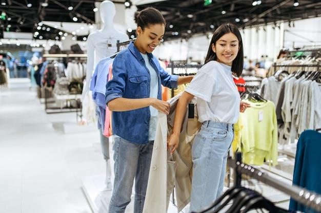 衣料品店でコートをしようとしている2人の女の子