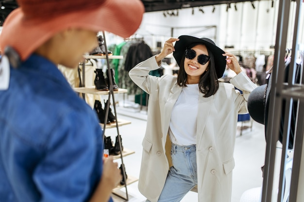 衣料品店で帽子をかぶっている2人の女の子