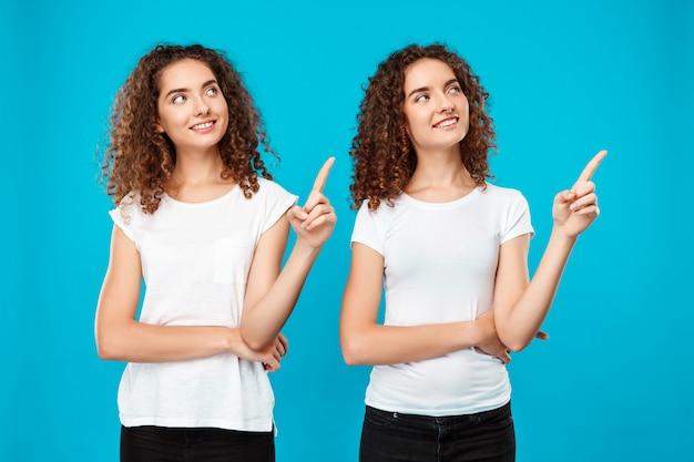 Две девочки-близнецы улыбаются, указывая пальцами на синюю стену