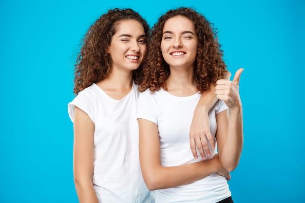 Две девочки-близнецы улыбаются, подмигивая, показывая, как над синей стеной