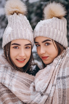 Two girls twins together in winter park