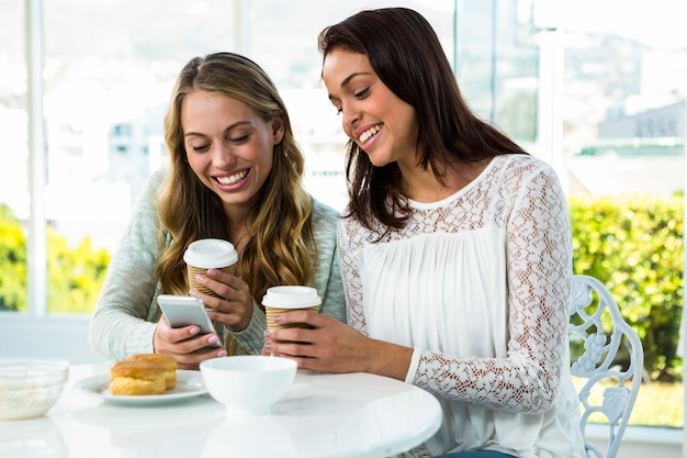 Two girls use a phone while eating and drinking