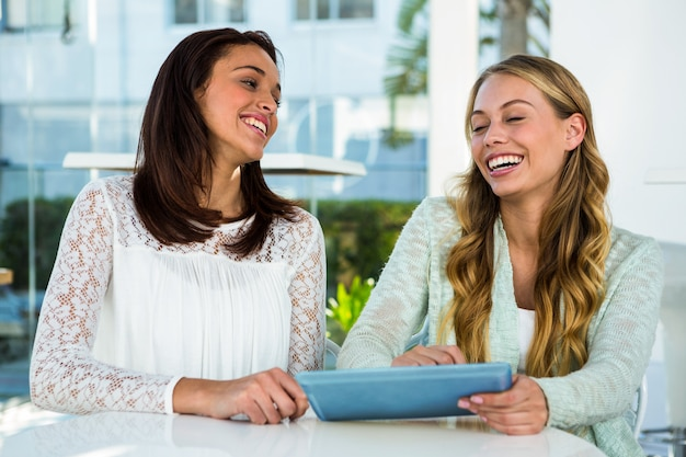 Two girls use a tablet and laughing