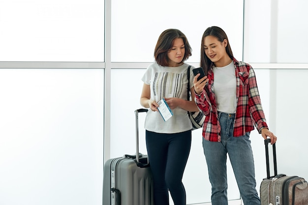 Two girls using smartphone checking flight or online check-in at airport, with luggage. air travel, summer holiday, or mobile phone application technology concept