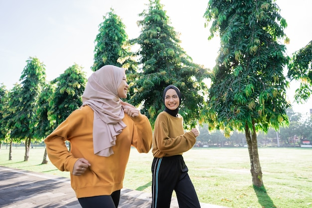 Two girls in veil do outdoor sports while jogging together in the garden with copyspace