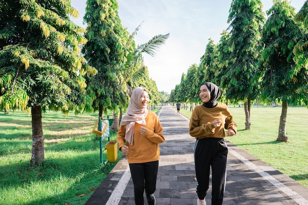 Two girls in veil do outdoor sports while jogging together in the garden