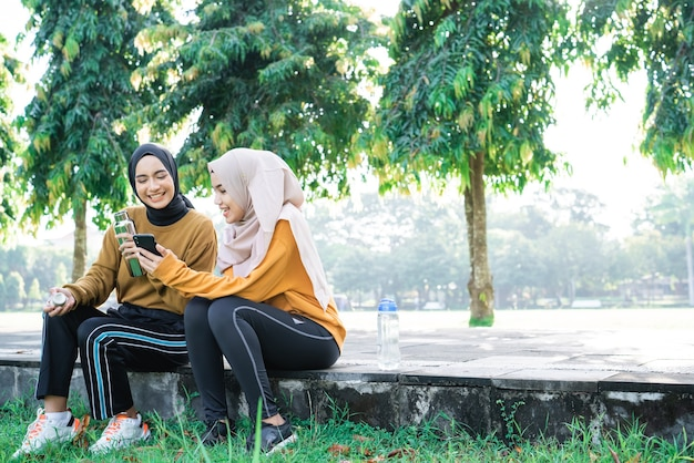 Two girls in veil sits with chatting when exercise breaks while using handphone and drink water with bottle in the park