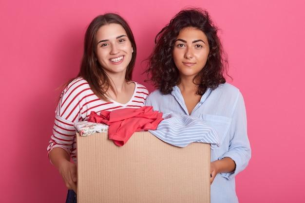 Две девушки-волонтеры держат бумажную коробку с одеждой для бедных