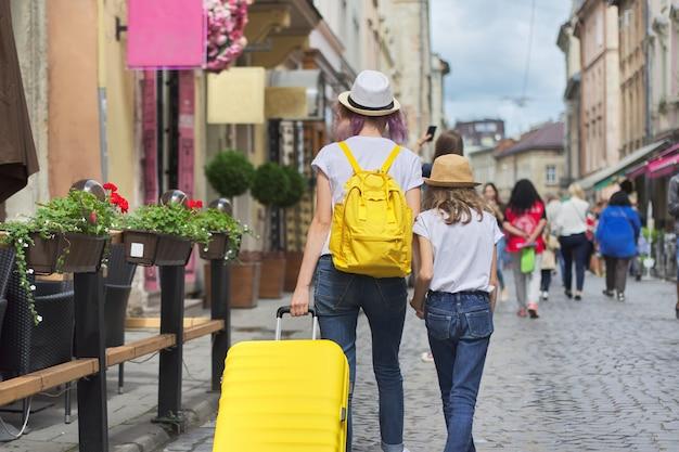 スーツケース、背面図が付いている都市を歩く2人の女の子