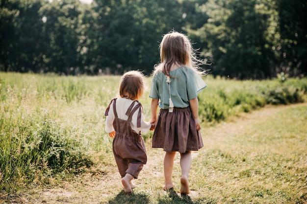 パス、裸足、手をつないで歩く二人の女の子