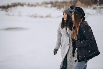 Две девушки гуляют в зимнем парке
