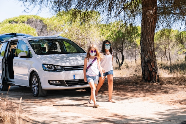 Two girls walking with bright sunglasses and face mask after a stop on the summer vacation road trip in the middle of the covid19 coronavirus pandemic on a sandy pine road